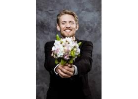 年轻帅气的新郎笑容满面手捧新娘花束_7591063