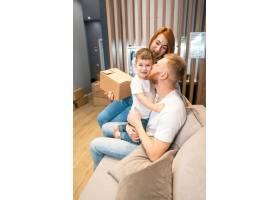 年轻幸福的家庭带着孩子一起坐在沙发上打开_6440940