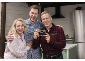 幸福的一家人在厨房里拿着相机_6609164