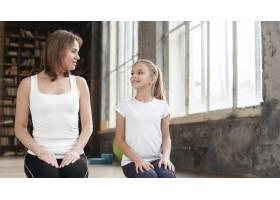 中间镜头妈妈和女孩坐在瑜伽垫上_7334039
