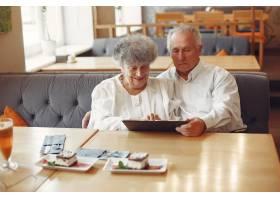优雅的老两口在咖啡馆里用平板电脑_7590225