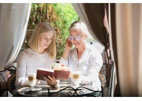 美丽成熟的母亲和她的女儿手持杯子坐在家里_7402522