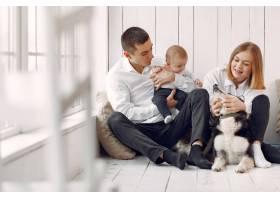 美丽的一家人在卧室里和一只狗共度时光_7397465