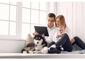 美丽的一家人拿着平板电脑在卧室里度过时光_7397622