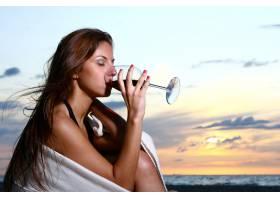 美丽的年轻女子在海滩上喝酒_6451670