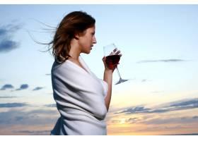美丽的年轻女子在海滩上喝酒_6451671