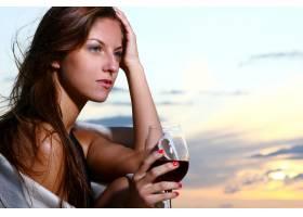 美丽的年轻女子在海滩上喝酒_6451676