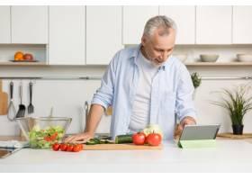 英俊成熟的男子站在厨房做沙拉_7285989