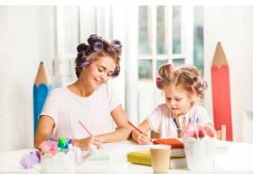这位年轻的母亲和她的小女儿在家里用铅笔作_7570511