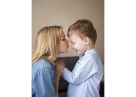 金发妈妈亲吻她可爱的小男孩_7146593