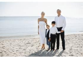 阳光明媚的夏日沙滩上的非正式全家福父母_7249565