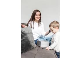 面带微笑的母亲和孩子坐在沙发上_7089415