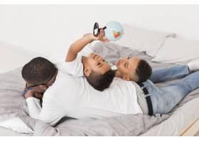 高角家庭一起在床上玩着一个小地球仪_7119888