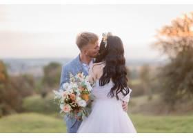 温柔的新娘和新郎傍晚在户外的草地上亲吻_7497974