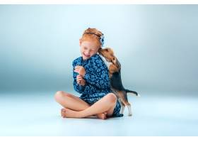 灰墙上快乐的女孩和一只小猎犬_7540144