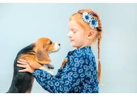 灰墙上快乐的女孩和一只小猎犬_7540148