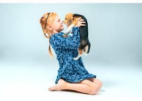 灰墙上快乐的女孩和一只小猎犬_7540149