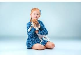 灰墙上快乐的女孩和一只小猎犬_7540150
