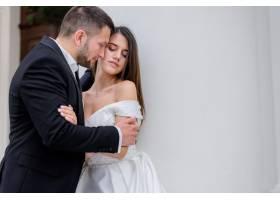 热情洋溢的新人身着婚纱站在白墙旁婚姻观_7497132