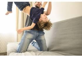 父亲和儿子在沙发上玩耍_7553266