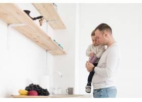 父亲在厨房抱着孩子的侧视_7089336