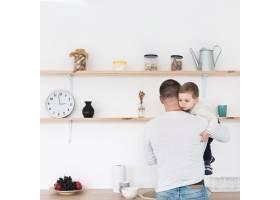 父亲在厨房抱着孩子的背影_7089342