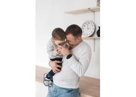 父亲在厨房里抱着他的孩子和马克杯_7089305