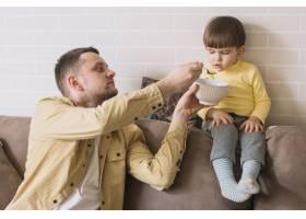 父亲在客厅给儿子喂奶_7496358