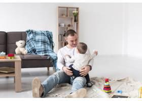 父亲在家中带着婴儿和玩具的前景_7089368