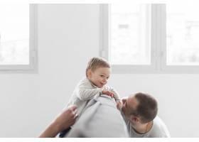 父亲在家里和快乐的婴儿玩耍_7089411