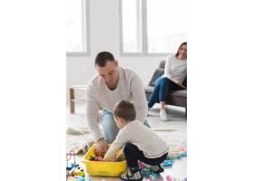 父亲带着孩子玩耍母亲则在一旁看着_7089351