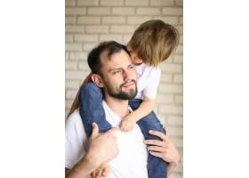 父亲把孩子抱在肩上_7553247