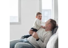 父亲抱着婴儿坐在沙发上的侧视_7089408