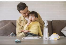 父亲看着桌子上的儿子和医用口罩_7496366