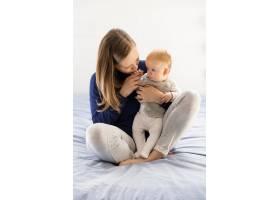 新妈妈拥抱亲吻可爱的宝宝_7552580