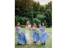 新娘和三个穿着蓝色连衣裙的伴娘在绿色公园_7498715
