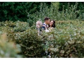新婚快乐的新人在高高的绿色灌木丛中微笑接_7497996