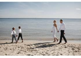 时尚一家走在风平浪静的海边父母和孩子手_7249547