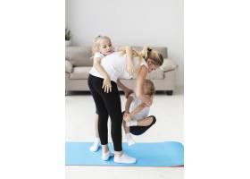 母亲一边锻炼一边和女儿在家里玩耍_7435945