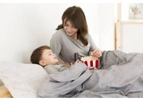 母亲和儿子在床上吃爆米花_6881454
