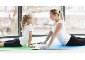 母亲和女儿在家中瑜伽垫上的侧观_7435928