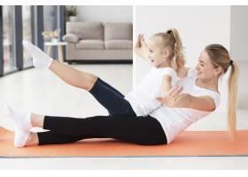 母亲和女儿在家在瑜伽垫上锻炼的侧观_7435925