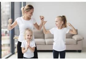 母亲和女儿在家里炫耀他们的二头肌_7435884