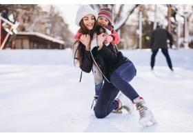 母亲和女儿在溜冰场上教滑冰_6641653