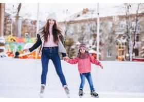 母亲和女儿在溜冰场上教滑冰_6641657