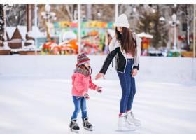 母亲和女儿在溜冰场上教滑冰_6641658