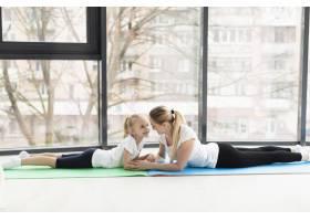 母亲和孩子在家中瑜伽垫上的侧观_7435765