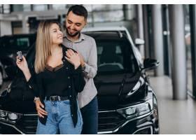 年轻夫妇在汽车展厅选车_7168678