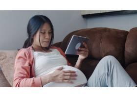 年轻的亚洲孕妇使用平板电脑搜索怀孕信息_6139076