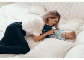 年轻的母亲在卧室里和可爱的孩子儿子一起开_7303070
